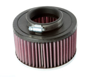A sutdio shot of an automotive air filter for an engine, against a white background. This car part is a commonly replaced component during servicing.
